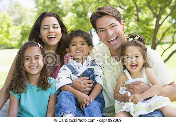 Family sitting outdoors smiling - csp1892069