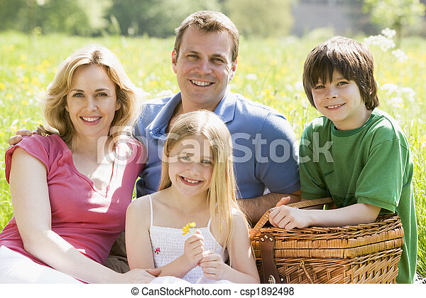 Family sitting outdoors with picnic basket smiling - csp1892498