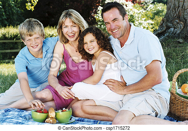 Family sitting outdoors with picnic smiling - csp1715272