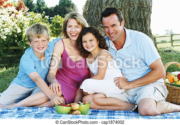 Family sitting outdoors with picnic smiling - csp1874002