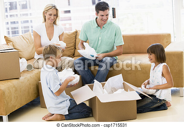 Family unpacking boxes in new home smiling - csp1715531