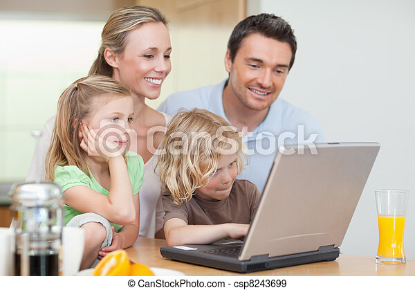 Family using the internet in the kitchen - csp8243699