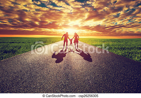 Family walk on long straight road, way towards sunset sun - csp26256305