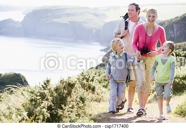 Family walking on cliffside path holding hands and smiling - csp1717400