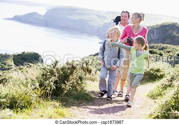 Family walking on cliffside path pointing and smiling - csp1873987