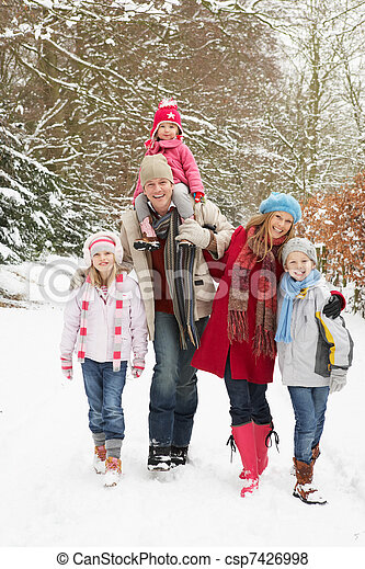 Family Walking Through Snowy Woodland - csp7426998