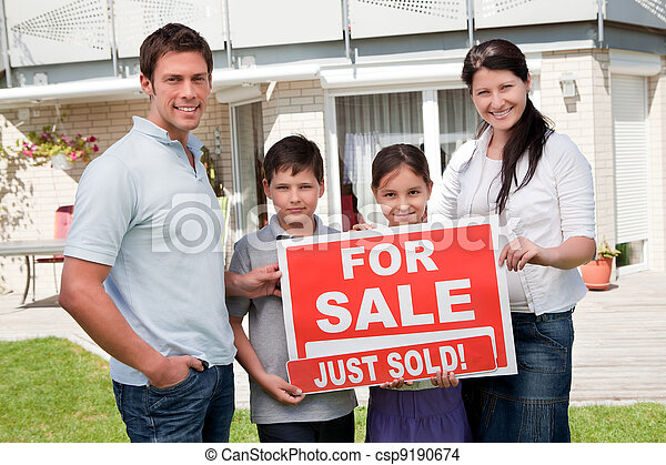 Family with a sale sign outside their new home - csp9190674