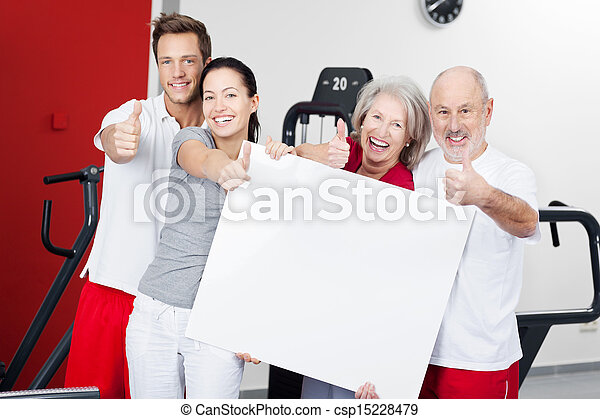 Family With Blank Billboard Gesturing Thumbs Up In Gym - csp15228479