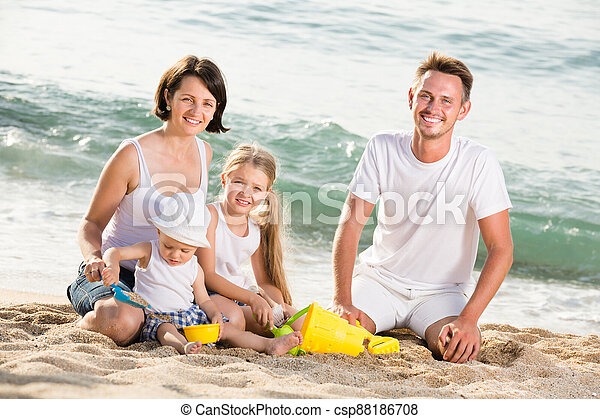 Family with children playing at beach - csp88186708