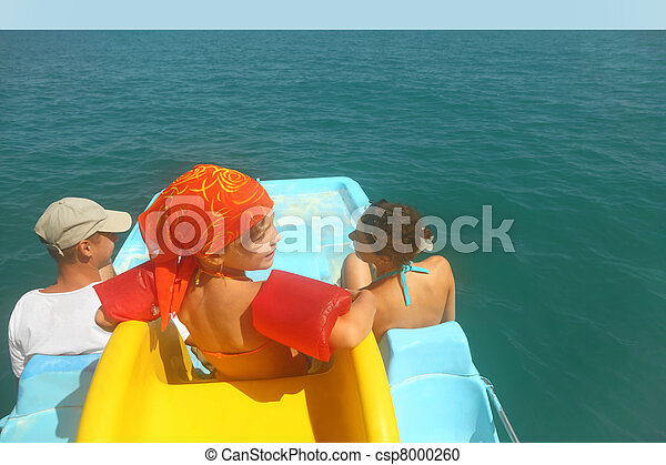 family with girl on pedal boat with yellow slide in sea, view from back on horizon, waterproof case - csp8000260