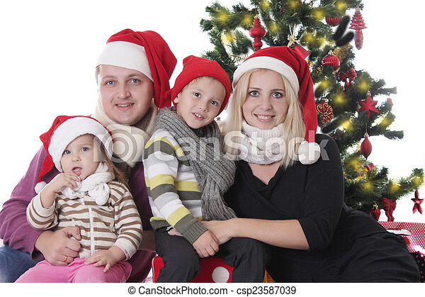 Family with two children sitting under Christmas tree - csp23587039
