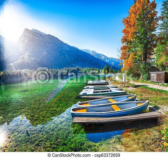 Fantastic autumn morning at Hintersee lake. Few boats on the lake - csp63372659