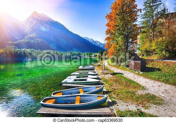 Fantastic autumn morning at Hintersee lake. Few boats on the lake - csp63369530