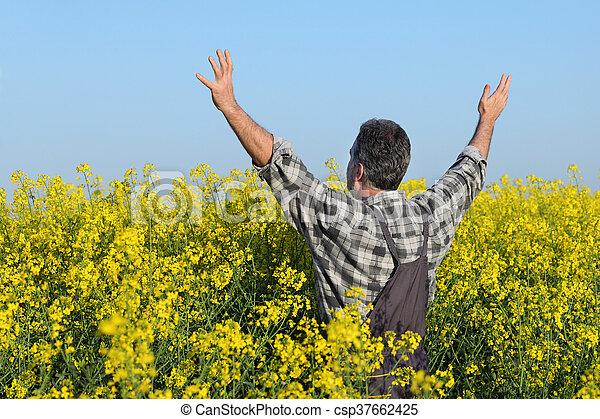 Farmer gesturing in rapeseed field - csp37662425
