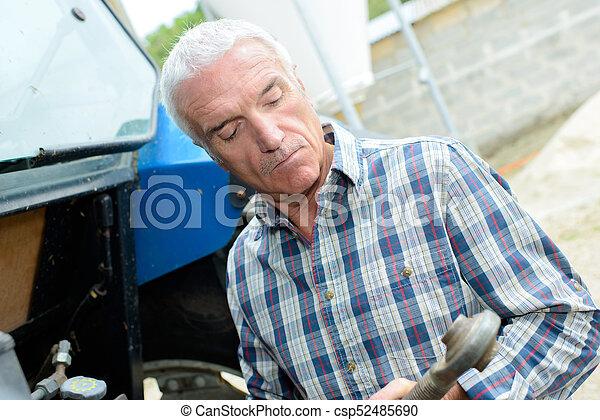 Farmer holding tractor pto shaft - csp52485690