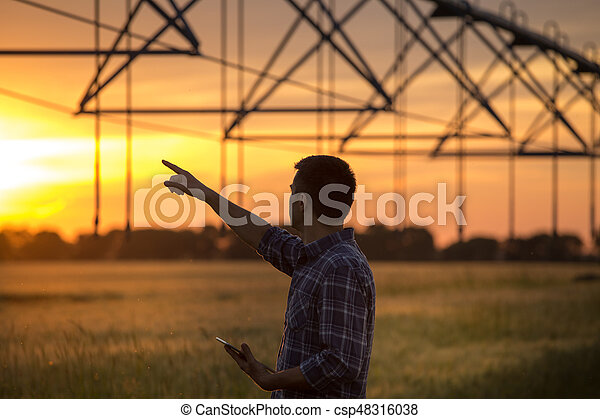 Farmer looking at irrigation system in field at sunset - csp48316038