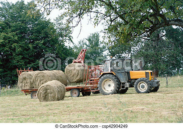 Farmer on his tractor picking up haystacks in Savoy, France - csp42904249