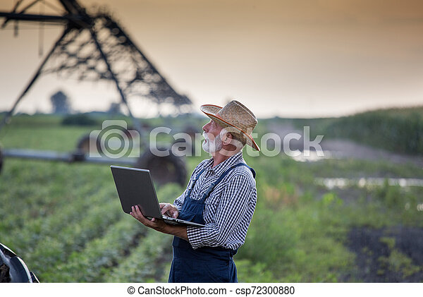 Farmer with laptop in front of irrigation system in field - csp72300880