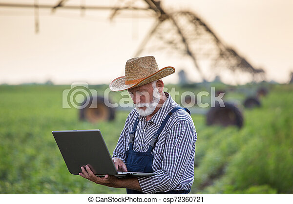 Farmer with laptop in front of irrigation system in field - csp72360721