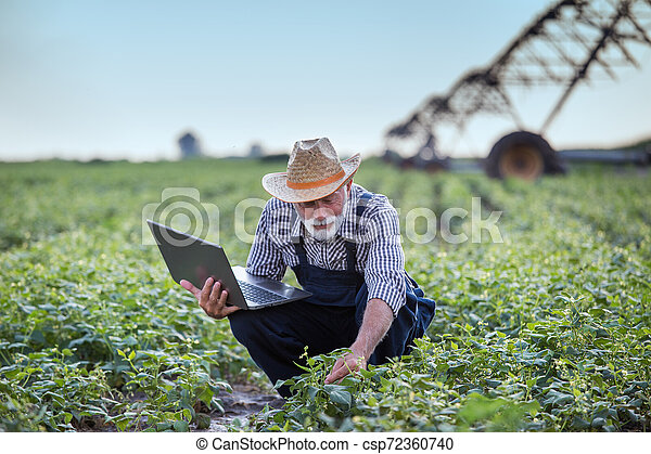 Farmer with laptop in front of irrigation system - csp72360740