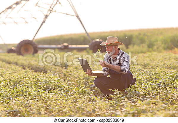Farmer with laptop in front of irrigation system - csp82333049