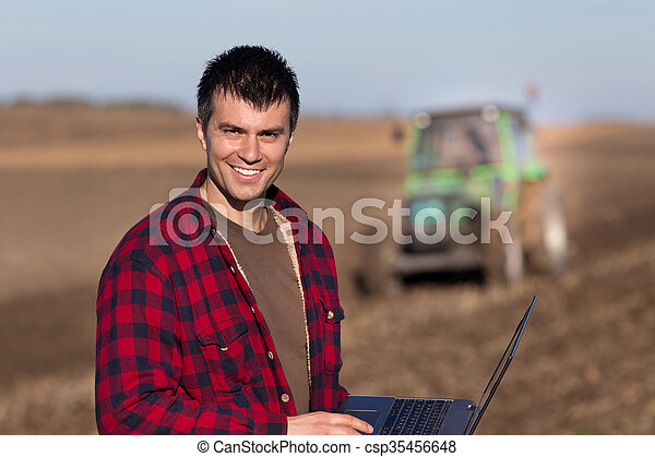 Farmer with laptop in the field - csp35456648