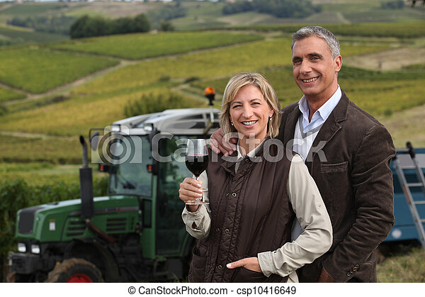 Farming couple stood in field in front of tractor - csp10416649
