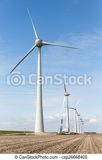 Farmland with construction work at the biggest windfarm of the Netherlands - csp26668405