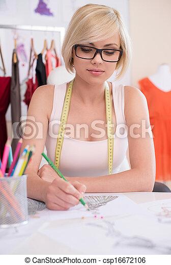 Fashion designer at work. Confident young fashion designer drawing sketch  - csp16672106