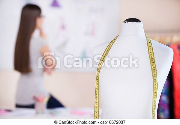 Fashion designer at work. Rear view of beautiful young woman looking at her sketches and holding hand on chin - csp16672037