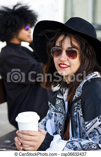 fashion girl drinking coffee on the street - csp36632437