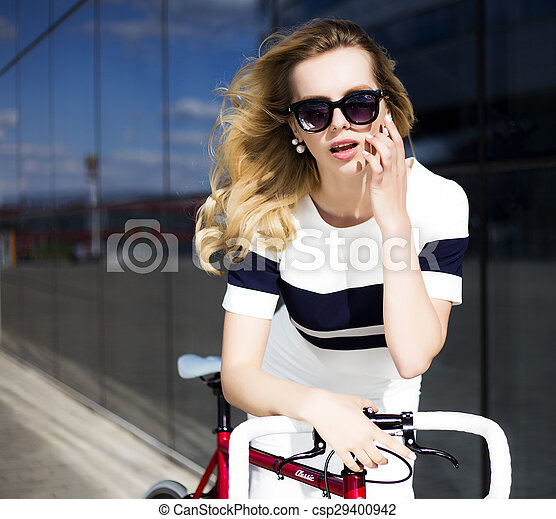 Fashion model in sunglasses poses near bicycle otdoors - csp29400942