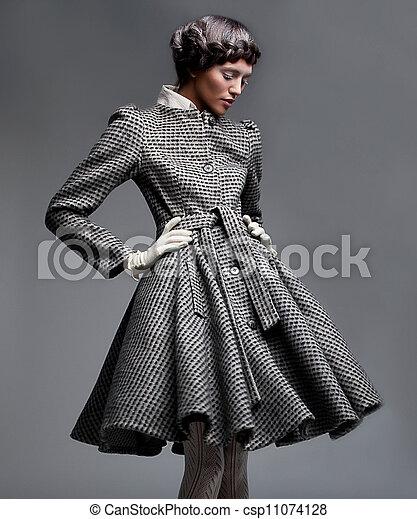 Fashion model lovely brunette in retro apparel posing in studio - csp11074128