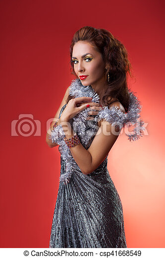 ef3aac369b7 Fashion photo of beautiful sensual woman with long dark hair in luxurious  dress in studio against red beckground wearing cristmas decoration for new  year ...