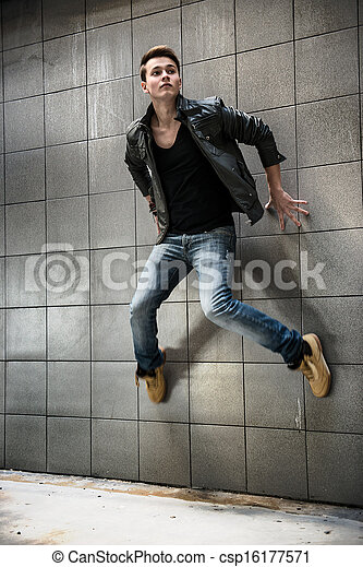 fashion photo of handsome man jumping on the street wall - csp16177571