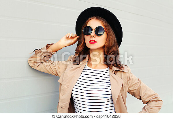 edf0942c6fd Fashion portrait beautiful young woman with red lips wearing a black hat  sunglasses coat over grey