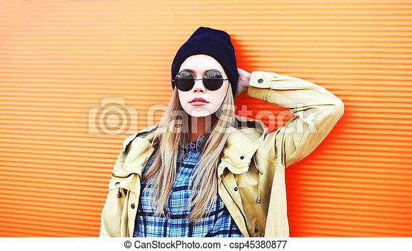cb2339e758d Fashion portrait pretty blonde woman in black sunglasses and hat on a  colorful orange background closeup