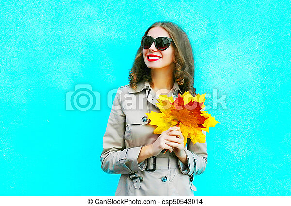 Fashion portrait smiling woman with autumn yellow maple leaves on a blue background - csp50543014