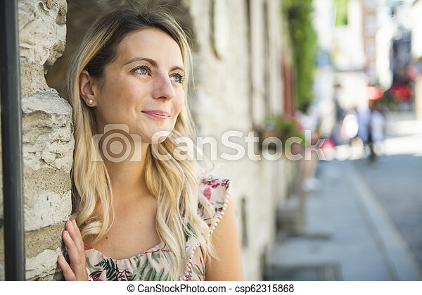 Fashion woman portrait of young pretty trendy woman posing on the quebec city street - csp62315868