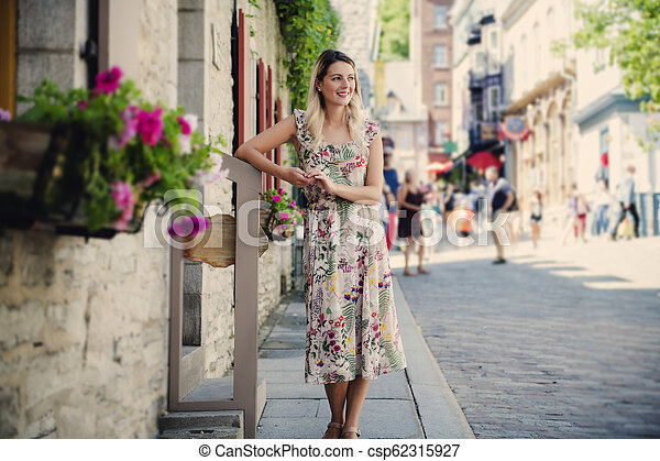 Fashion woman portrait of young pretty trendy woman posing on the quebec city street - csp62315927