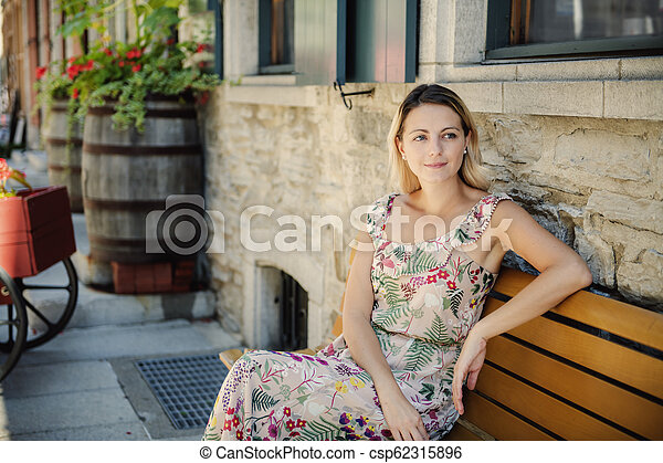 Fashion woman portrait of young pretty trendy woman posing on the quebec city street - csp62315896