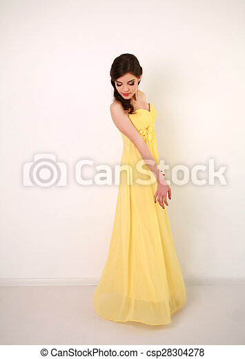 Fashion young woman in long yellow dress, studio on white - csp28304278