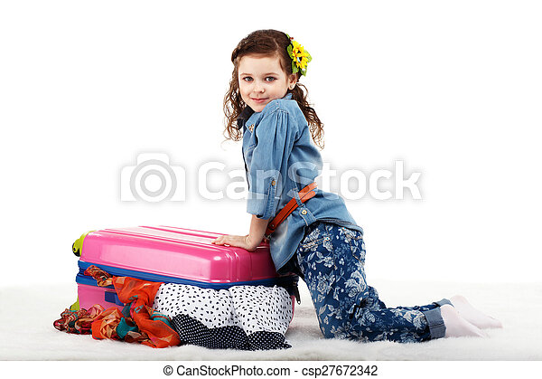 Fashionable little girl closes the suitcase with clothes - csp27672342