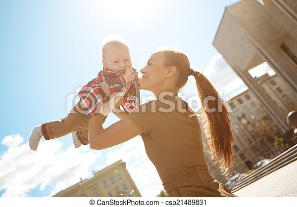Fashionable modern mother on a urban street with a pram. Young m - csp21489831