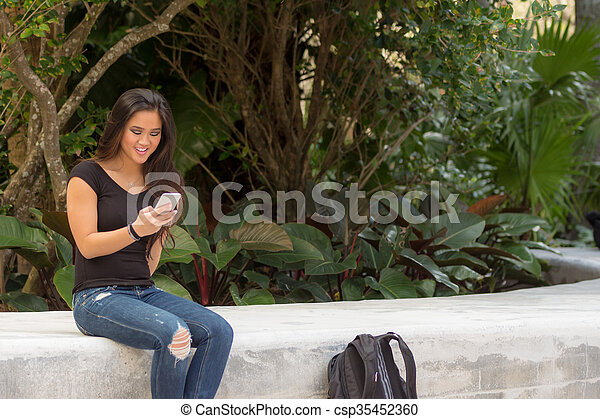 Fashionable smiling young pretty Asian woman on school campus texting on smart phone - csp35452360