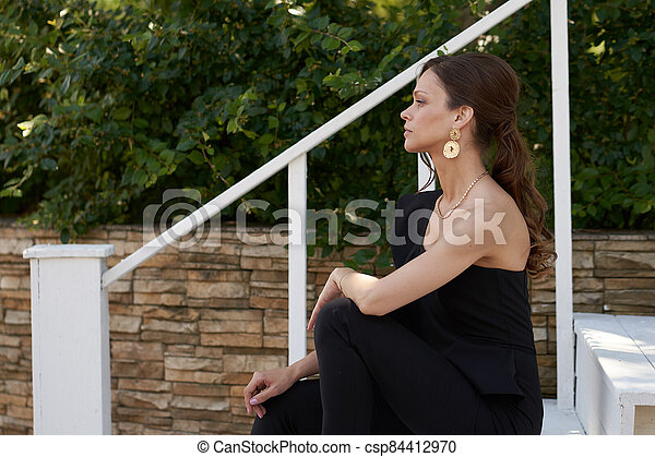 Fashionable woman in a black dress and golden earrings in the city - csp84412970