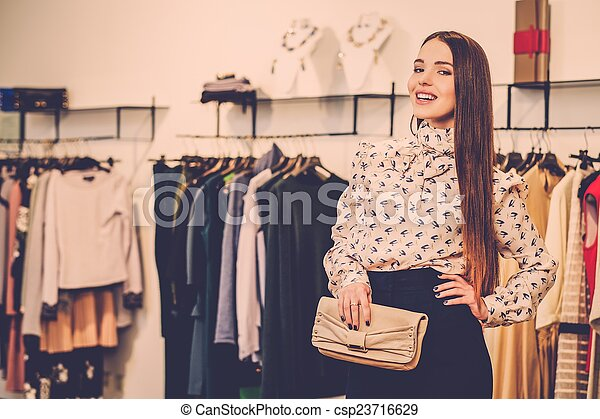 Fashionable young woman in a fashion showroom - csp23716629