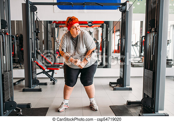 fat sweaty woman using exercise machine in gym calories