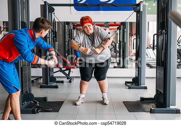fat woman training with instructor hard workout fat