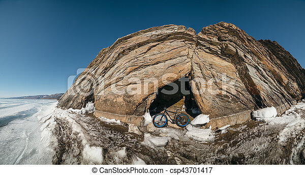 Fatbike (also called fat bike or fat-tire bike) - Cycling on large wheels. Teen rides a bicycle through the snow mountains in the background.